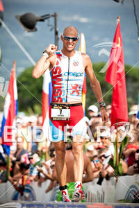 2010 Kona Ford Ironman World Championships Dirk Bockel 7 LUX crosses finish line KSwiss Larry Rosa