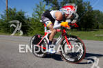 Age group athlete Winfield Hartley on bike with big orange…