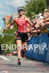 Meredith Kessler hi-fves the crowd as she wins  the Ironman…