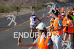 Volunteer hands off Tim O'Donnell some water on the bike…