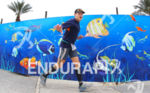 Triathlete running front of an aquarium cartoon