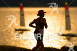 Age Group athlete running past scenic Lake Taupo at sunset,…