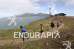 Athletes run along the coast at the 2013 Escape from…