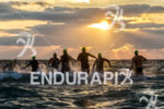 Triathletes jumping into the water against a beuatiful sunrise at…