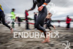 Athletes exit the water and run to T1 at the…