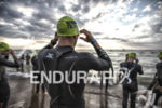 Professional triathletes entering water for the swim start at the…