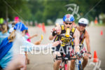 Age group athlete takes in nutrition at an aid staion…