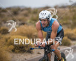 Christian Kemp riding in the rain at the 2013 Ironman…