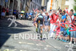 Sebastian Kienle on the bike with cheering spectators climbing a…