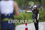 A volunteer directs runners during the run leg at the…