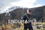 Athlete running with the iced mounain on the background at…