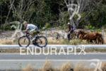 Age grouper riding with horses during the bike portion of…