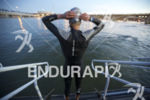 A pro triathlete prepares to enter the water and swim…