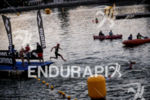 Age group athlete jumping in the water during the rolling…