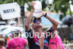 An athlete gets hydration during the run portion of the…