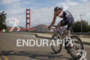 Andy Potts bikes past the Golden Gate Bridge at the…