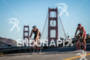 Age group athletes bike past the Golden Gate Bridge during…