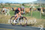 An age grouper athlete cycles past a field of dairy…
