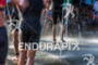 Athletes run through showers after exiting the water after the…