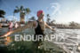 Female athlete warms up before swimming to the swim start…
