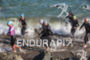 Age group athletes fight the strong currents and waves as…