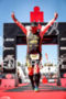 Age group athlete crossing the finish line of the Ironman…